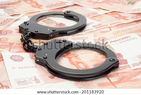 financial crime. Steel handcuffs and money - stock photo