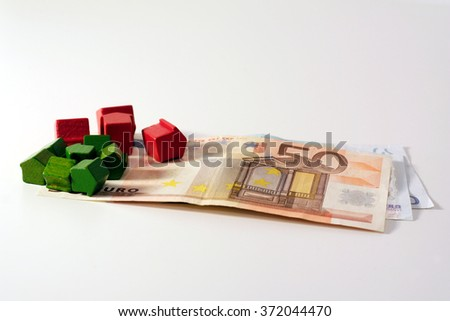 Financial crisis and housing market. Euro banknotes and tiny wooden houses - stock photo