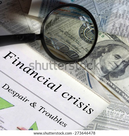 Financial crisis headlines. Magnifying glass and one hundred dollar bill in the background. - stock photo