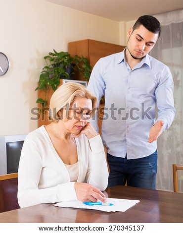 Financial crisis in family of upset adult son and his senior mature mother