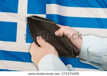 Financial Crisis in Greece - Man's Hand With Empty Wallet and Greek flag - stock photo