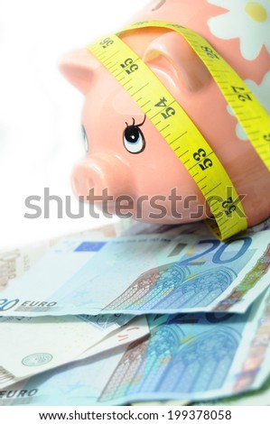 Financial crisis metaphor with piggy bank and measuring tape  - stock photo