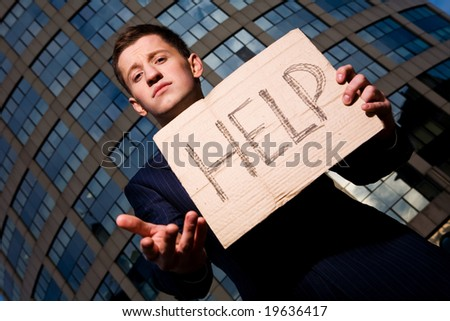 Financial crisis. Unemployment. Businessman holding sign Help outdoors - stock photo
