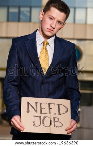 Financial crisis. Unemployment. Young businessman holding sign Need Job outdoors - stock photo