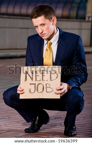 Financial crisis. Unemployment. Young businessman squatting with sign Need Job outdoors - stock photo