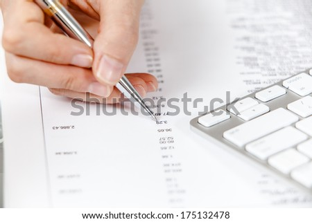 Financial data analyzing. A calculator, pen and financial statement.