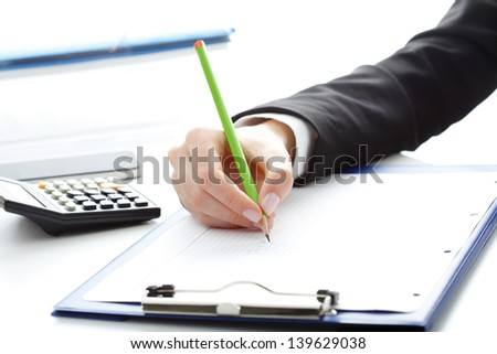 Financial data analyzing. Close-up photo of a businesswoman's hand writing and counting on calculator in office.  Selective focus - stock photo