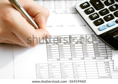 Financial data analyzing. Counting business data on the table closeup