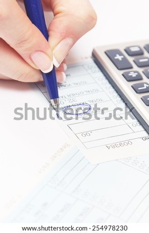 Financial data analyzing. Counting on calculator. A hand with a blue pen. - stock photo