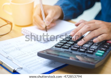 Financial data analyzing hand writing and counting on calculator in office   on wood desk