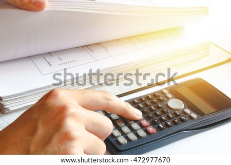 Financial data analyzing. savings, finances, economy. Close-up photo of a businessman's hand counting on calculator in office or home. Soft focus