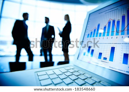 Financial document in laptop on background of three business partners interacting - stock photo