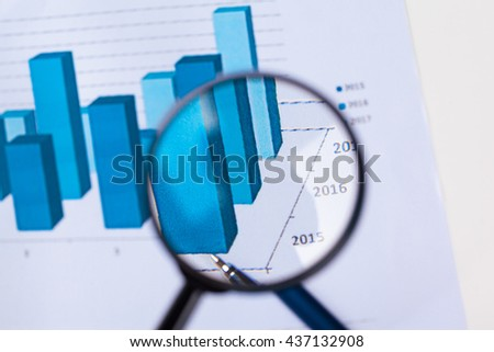 financial documents with magnifying glass over them - stock photo