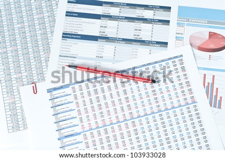 financial documents with red pen over them