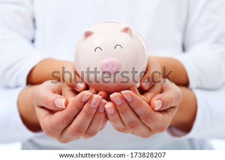 Financial education concept - adult and child hands holding smiling piggy bank