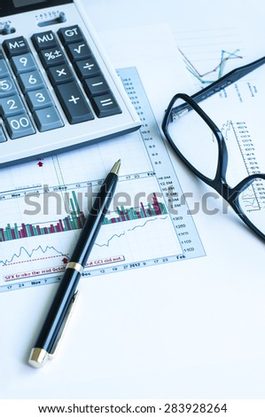 Financial graph analysis with calculator ,pen and glasses.