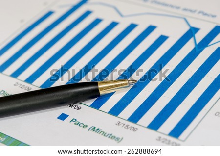 Financial graphs analysis and pen.
