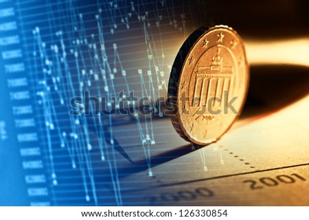 Financial graphs and coin. - stock photo