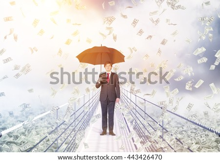 Financial growth and success concept with businessman holding umbrella and standing in the middle of bridge with abstract dollar banknote rain on cloudy background with sunlight - stock photo