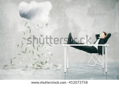 Financial growth concept with businessman sitting at table with feet up and looking at abstract money rain in concrete room - stock photo