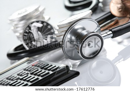 Financial health concept, stethoscope weaving around stacks of silver and gold coins and calculator