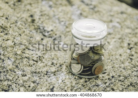 Financial image concept of coin in glass jar on the rock. blurred background with rock texture.low contrast and color tone applied - stock photo