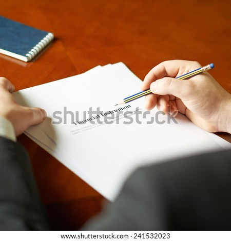 Financial instrument definition as a shallow depth of field close-up composition of a man in a business suit working with the text