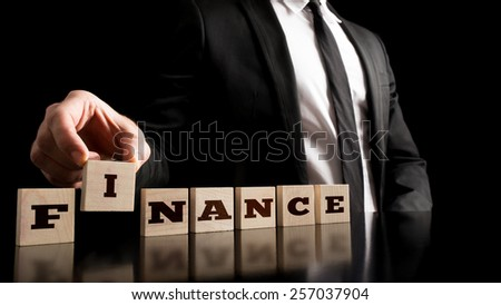 Financial market concept - Businessman Arranging Small Wooden Blocks with word Finance on a Pure Black Background. - stock photo
