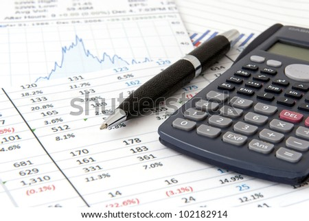 Financial objects: Stock chart,  calculator and pen - stock photo
