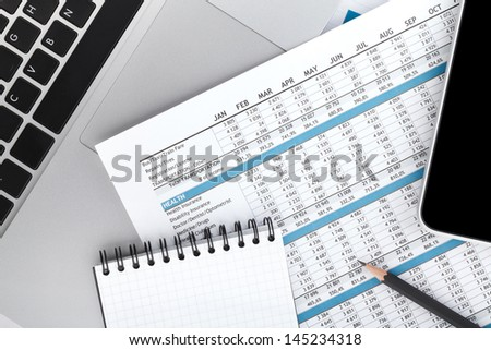 Financial papers, computer and office supplies closeup - stock photo