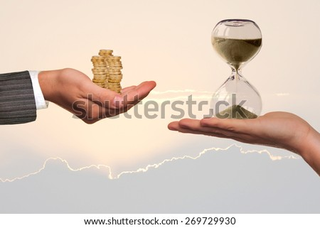 Financial planning concept. Hands holding hourglass and coins. - stock photo