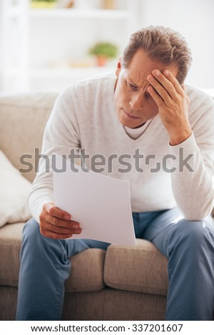 Financial problems. Frustrated mature man holding paper and looking at it while sitting on the couch at home