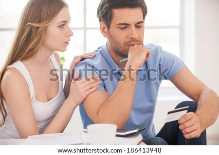 Financial problems. Frustrated young man holding plastic card while sitting close to his wife at their apartment  - stock photo