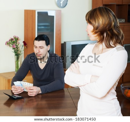 Financial problems in family. Man counting cash, wife watching him in home - stock photo