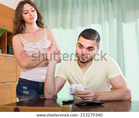 Financial problems in family. Man counting money, woman watching him in home  - stock photo