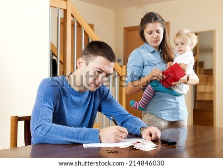 Financial problems in family. Sad woman wit baby against husband at table with money