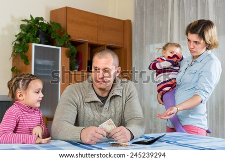 Financial problems in family. Unhappy young woman with children against husband  - stock photo