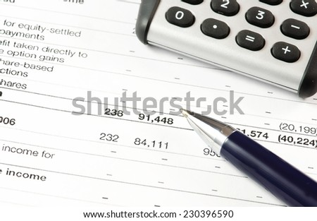 Financial report. Calculator and pen on a business background. - stock photo