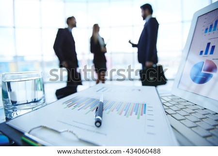 Financial report, computer and glass of water on the table with business people in the background