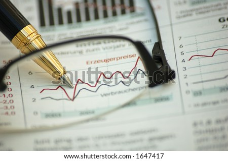 Financial report through reading glasses - focus on pen and report (not on glasses)