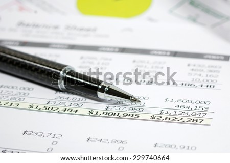 Financial report with black pen