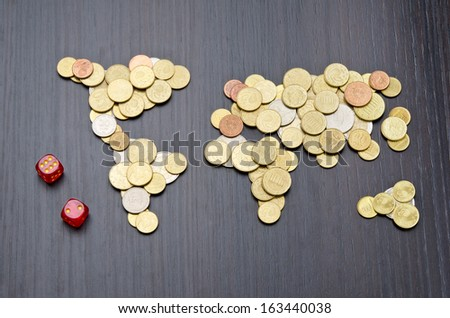 Financial risk. Office desk with world map made of money coins and two red dices - stock photo