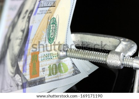 Financial Squeeze US currency money held tight in a clamp  - stock photo