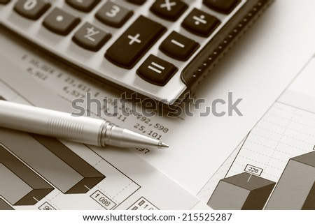 Financial statements. Business Graph. Ballpoint pen and calculator on a financial chart or Stock Market Data. Black and White (Sepia).