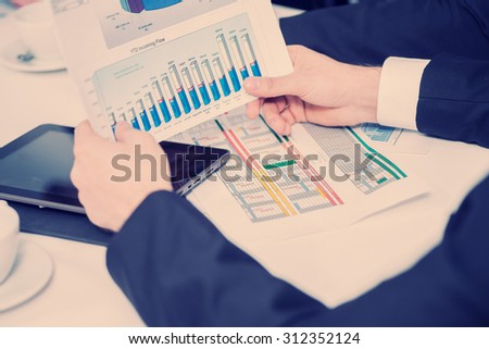 Financial statistics in hand. Four confident successful businessmen at a meeting while sitting at a table discussing business doing in the office - stock photo