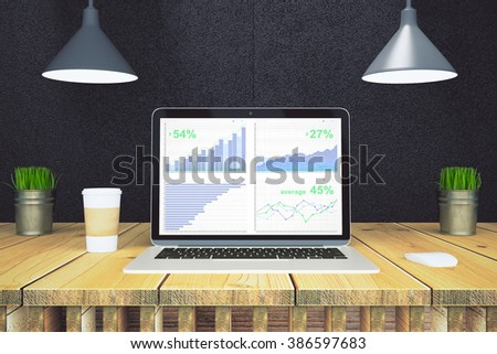 Financial statistics on laptop screen with paper cup of coffee on wooden table with black wall