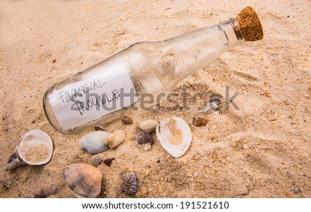 FINANCIAL TROUBLE message written on a piece of paper in a glass bottle on beach sand