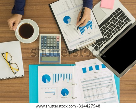 financial worker analyzing statistical data on desk in office. top view. Accounts concept. - stock photo