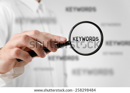 Find keywords concept. Marketing specialist looking for keywords (concept with magnifying glass).  - stock photo