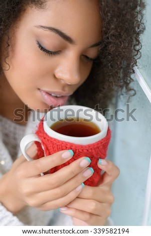 Find your harmony. Close up of delighted young charming girl holding cup and smelling aroma while drinking tea - stock photo